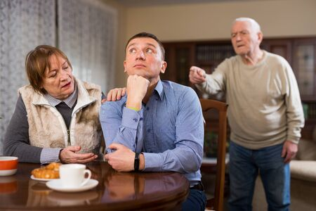 Senior man scolding his adult son in presence of mother in living room Stock fotó - 149359489