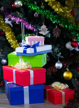 Pile of colorful gift boxes on background of decorated Christmas tree Фото со стока