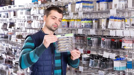 Man customer is considering fishing lures near stand in the sports shop