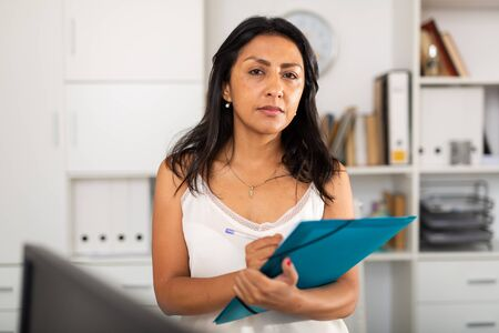 Portrait of successful Hispanic business woman writing down tasks in office