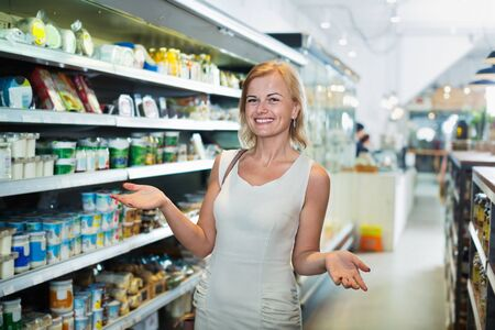 Smiling young woman standing among shelves in grocery store Imagens