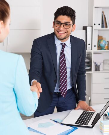 Manager of company meeting female client with handshake in workplace Standard-Bild