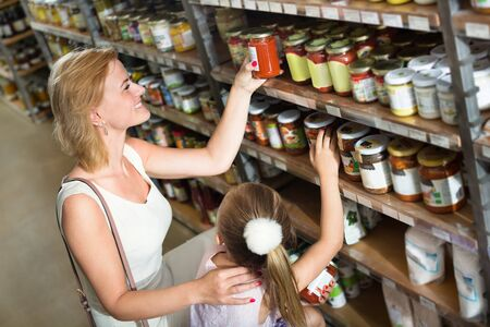 Glad young mother with daughter shopping a conserve crushed tomatoes in groceries