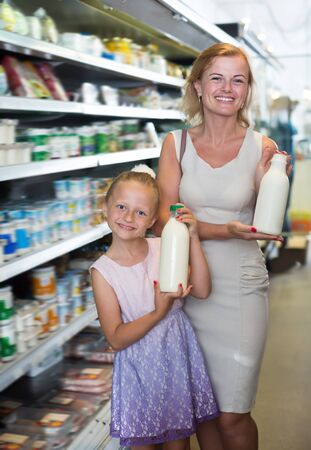 Portrait of smiling woman and girl holding bottle with fresh milk in grocery shop