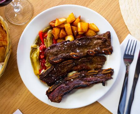 Appetizing grilled beef ribs served on white plate with fried potatoes and baked bell pepper Imagens