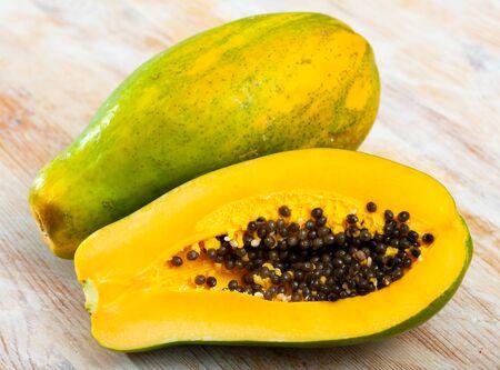 Closeup of whole and halved fresh ripe papaya on wooden surface. Tropical fruit Banco de Imagens