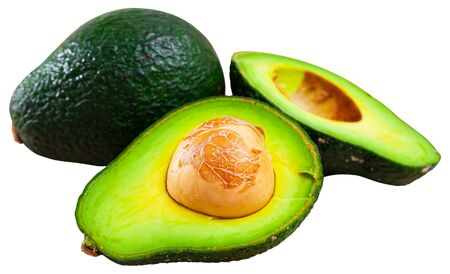 Whole and cut in half ripe organic avocados. Healthy vitamin nutrition concept. Isolated over white background