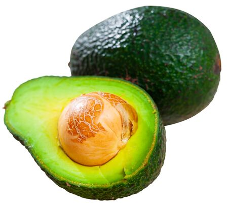 Closeup of whole and halved fresh ripe avocados. Healthy vegetarian ingredient. Isolated over white background
