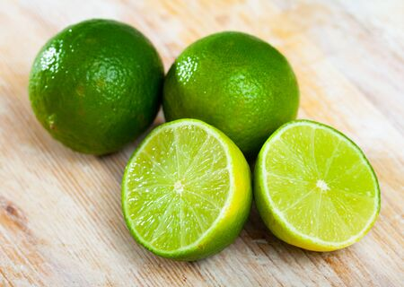 Sliced fresh juicy limes on wooden table. Concept of health benefits of citrus fruits