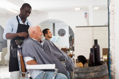 Skillful African-American barber putting on hairdresser cape to elderly male client sitting in haircut chair