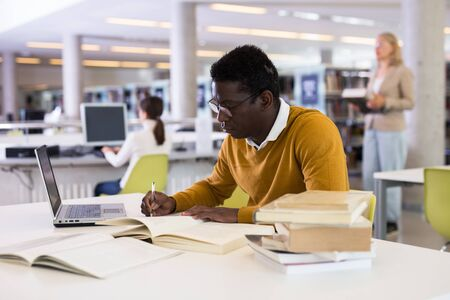 Confident african-american man working on laptop in public library