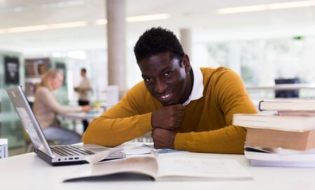Portrait of smiling african-american male student with laptop and book in public library