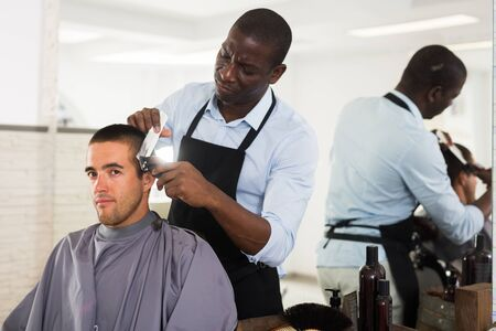 African-American hairdresser doing styling for young man with hair clipper at barber shop