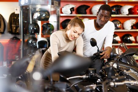 Cheerful positive smiling couple choosing and buying new motorcycle in moto salon
