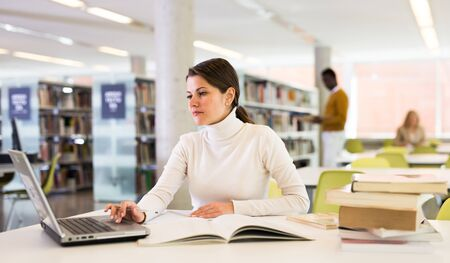 Portrait of smiling woman with laptop and book in public library Reklamní fotografie