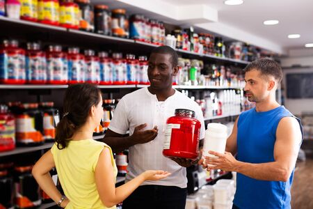 happy active physically fit people discussing modern sport nutrition products in shop
