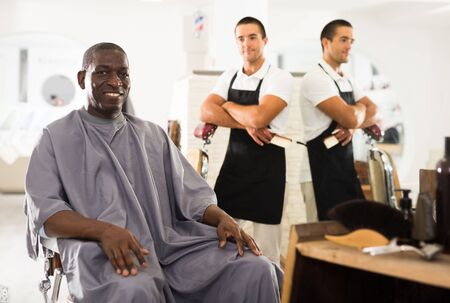 Delighted African male client sitting in hairdressing chair after haircut from professional barber Imagens