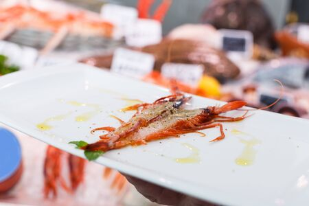 Closeup of fried big prawn with spices on white rectangular plate in hand of waiter