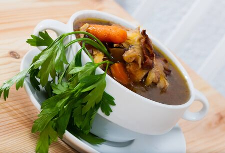 Scottish soup dish on peppered chicken stock with leeks, carrots and parsley (Cock-a-leekie) served on white plate