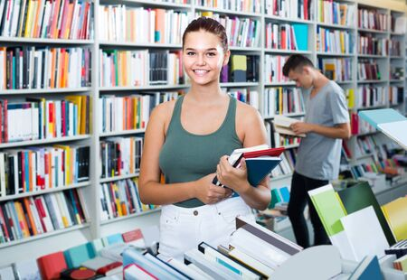 cheerful european teenage girl holding new books pile in shop