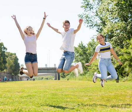 Friendly teenagers jumping together in park on spring