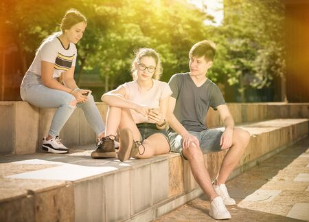 Teenagers having friendly discussion and using cellphones during gathering outdoors on summer day