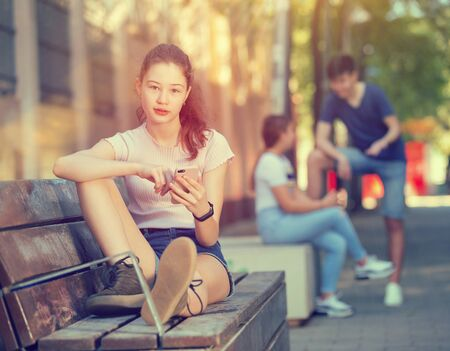 Portrait of cute teen girl carried away with smartphone outdoor on summer day
