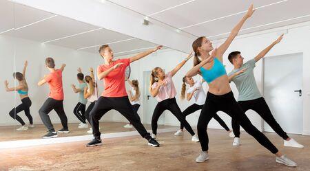 Garçons et filles joyeux d'adolescent dansant la chorégraphie de groupe synchrone dans la salle de danse