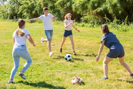 Happy teenage girls and guy playing football on green lawn in summer city park