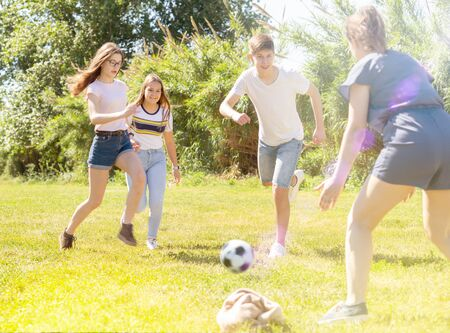 Cheerful teenagers are jogning with ball in spring park
