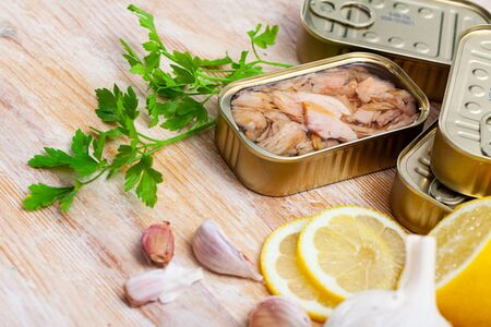 Tin can of natural chopped tuna belly in oil on wooden background with lemon, garlic and parsley