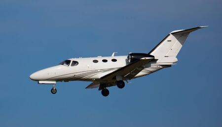 Modern comfortable private jet flying in blue sky, approaching landing