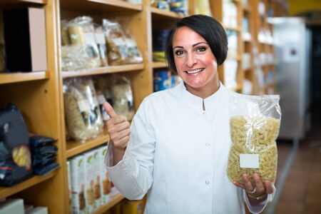 Smiling mature woman seller in uniform holding pasta package in hands in pharmaceutical store