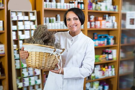 Portrait of cheerful female pharmacist with dried vulnerary plans in hands
