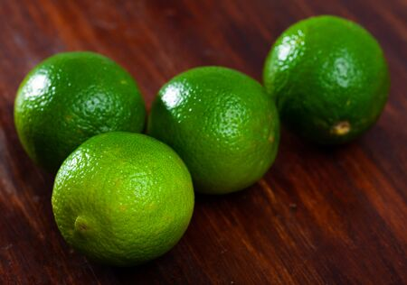 Closeup of whole ripe green limes on wooden table. Vitamin fruits