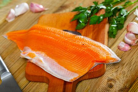 Fresh steelhead trout fillet on wooden surface with seasonings ready for cooking