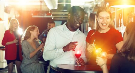 Couple of cheerful smiling male and female on party in the club with cocktails Foto de archivo