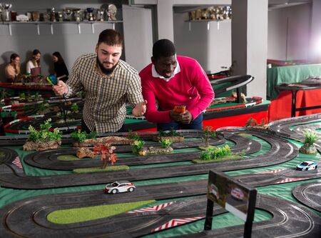 Two men with remote control playing race car models on the track