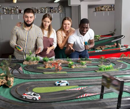 Two teams frompairs play slot car racing game