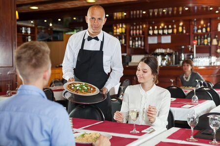 Smiling waiter serving delicious pizza to young couple in cozy restaurant