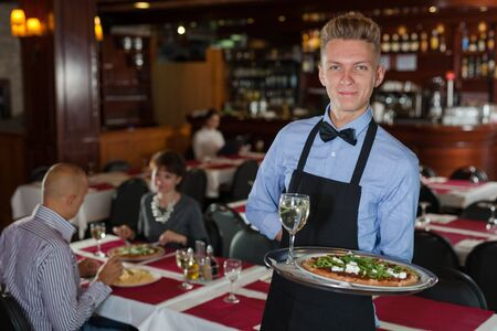 Handsome elegant waiter with serving tray welcoming to restaurant Archivio Fotografico - 150120704