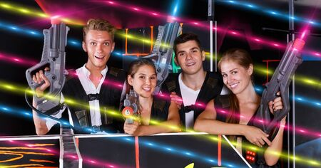 Group portrait of command players with pistols in their hands in dark laser tag room