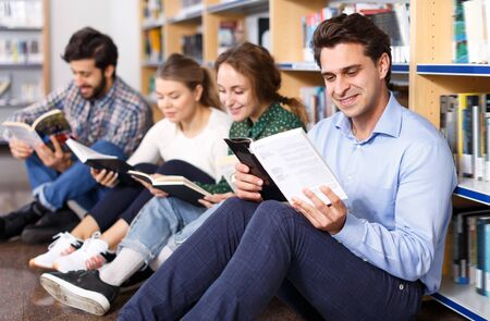 Smiling man reading book sitting on floor in public library with other young people on background with bookshelves