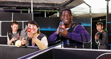 Portrait of young man and woman with laser pistols playing laser tag on dark labyrinth