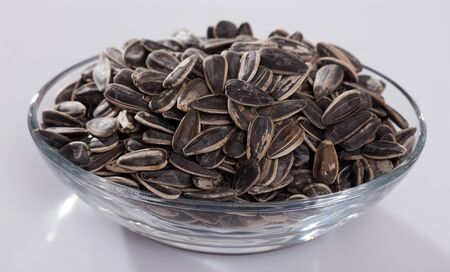 Glass bowl with sunflower seeds in hulls on white background. Popular snack food