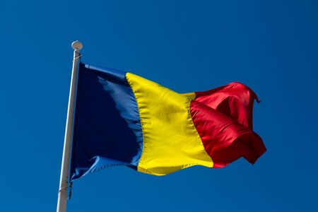 Romanian flag on flagpole waving against blue sky Foto de archivo - 150035757