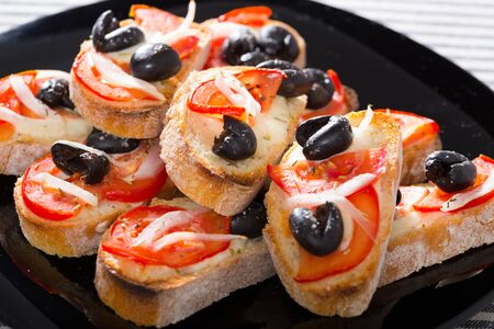 Delicious hot sandwiches with cream cheese sauce, tomatoes and black olives Foto de archivo
