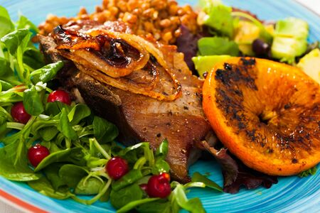 Delicious roasted pork shin served with stewed lentils, fresh avocado, greens and grilled orange