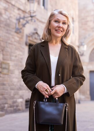 Portrait of an elegant elderly woman on spring street of european city