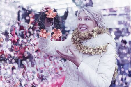 Portrait of happy  woman in tinsel choosing Christmas decoration at fair